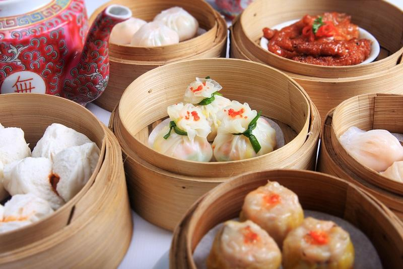 A variety of dim sum in bamboo steam containers.