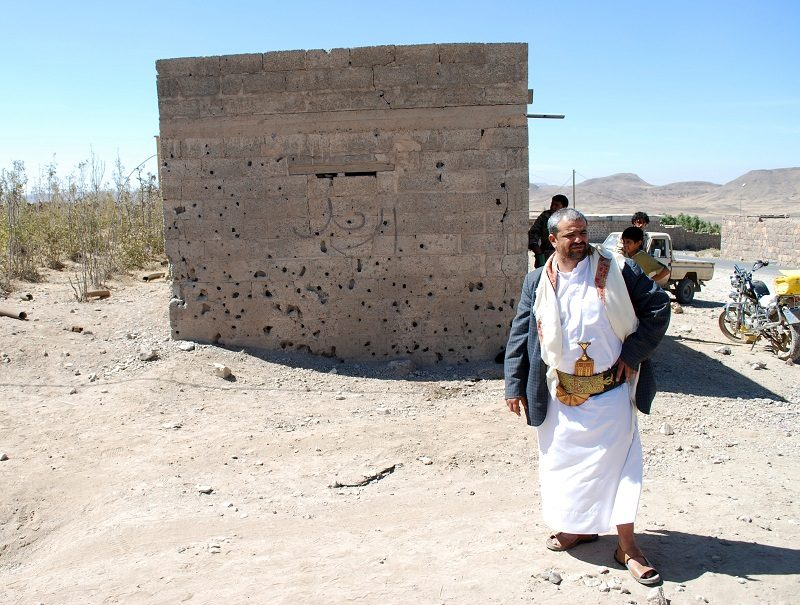 Himyar al Qadhi stands next to a building pockmarked by damage from the drone strike that killed his brother Adnan, who was targeted for his alleged ties to AQAP.