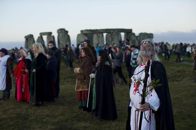 Druid leader Arthur Uther Pendragon, right, looks up as people face east to watch the sunrise by the ancient stone circle of Stonehenge on the annual Winter Solstice, Friday, Dec. 21, 2012.