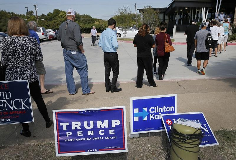 Early voters stand by campaign signage as they wait in line at a voting location, Thursday, Oct. 27, 2016, in Dallas.