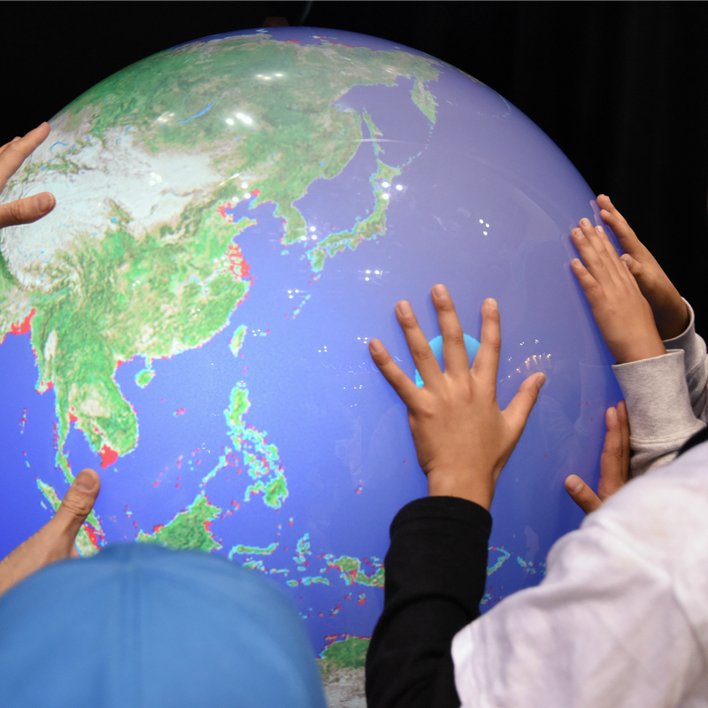 Schoolchildren touch an electronic globe to learn the rise in sea levels by global warming in Tokyo.