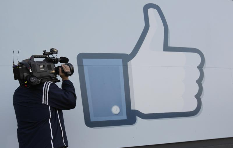 A television photographer shoots the Like sign outside of Facebook headquarters in Menlo Park, Calif., Friday, May 18, 2012.