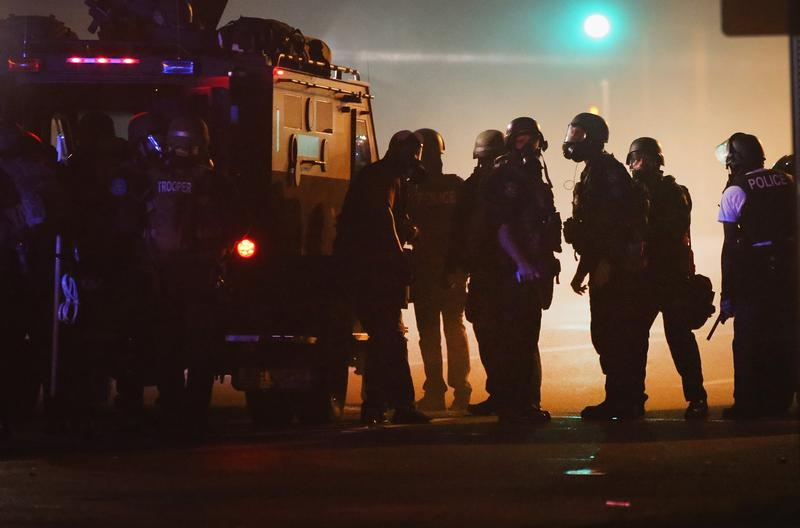 Police attempt to control demonstrators protesting the killing of teenager Michael Brown on August 18, 2014 in Ferguson, Missouri. Police shot smoke and tear gas to disperse the protestors with as th