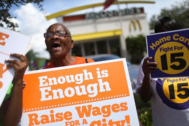 Laura Rollins joins with others to protest in front of a McDonald's restaurant in support of a $15 an hour minimum wage on September 10, 2015 in Fort Lauderdale, Florida.