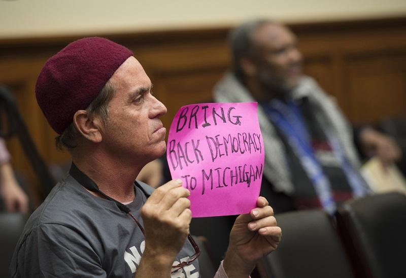 A Flint, Mich. resident holds a sign on Capitol Hill in Washington, Wednesday, 2/3/16, during the House Oversight and Government Reform Committee hearing to examine the ongoing situation in Flint.