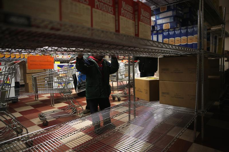 A child accompanies his grandmother choosing free groceries at a food pantry run by the Food Bank For New York City