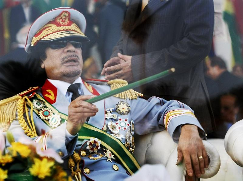 In this Tuesday, Sept. 1, 2009 file photo, Libyan leader Moammar Gadhafi gestures with a green cane as he takes his seat behind bulletproof glass for a military parade in Green Square, Tripoli, Libya.