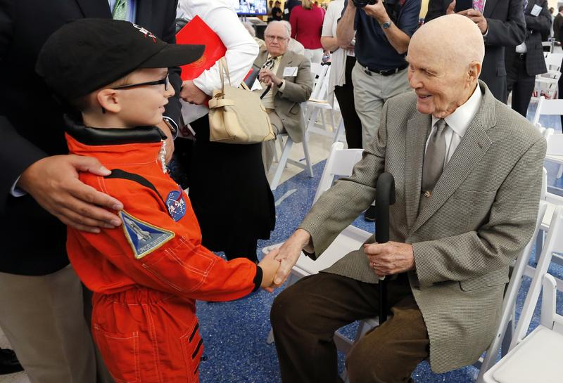 Former astronaut and U.S. Sen. John Glenn shakes hands with 8-year-old Josh Schick in June.