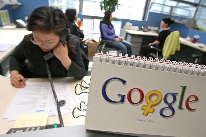 Google employees work by a calendar that features the company's logo changed a little for the month of March in honor of Woman's day (March 8), in their offices in Beijing, China, on March 2, 2006.