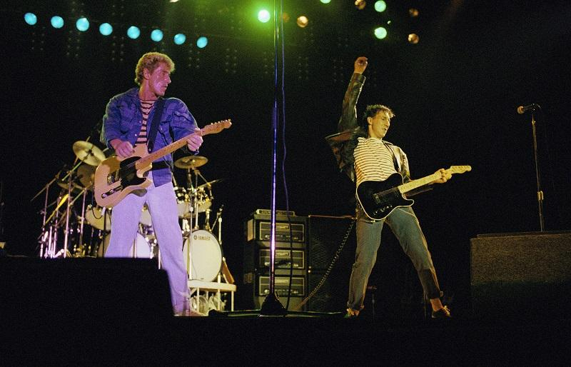 """Roger Daltrey watches as Peter Townshend, right, use a windmill motion to strum his guitar duringTthe Who"""" concert in the Seattle Kingdome on Wednesday, Oct. 21, 1982."""