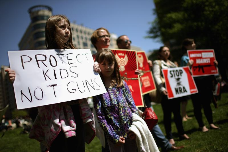 Anti-gun violence demonstrators, including Rachel Ahrens (L), 13, Abby Ahrens, 8, and their mother Betty Ahrens hold signs condeming the National Rifle Association during a protest in Washington, D.C.