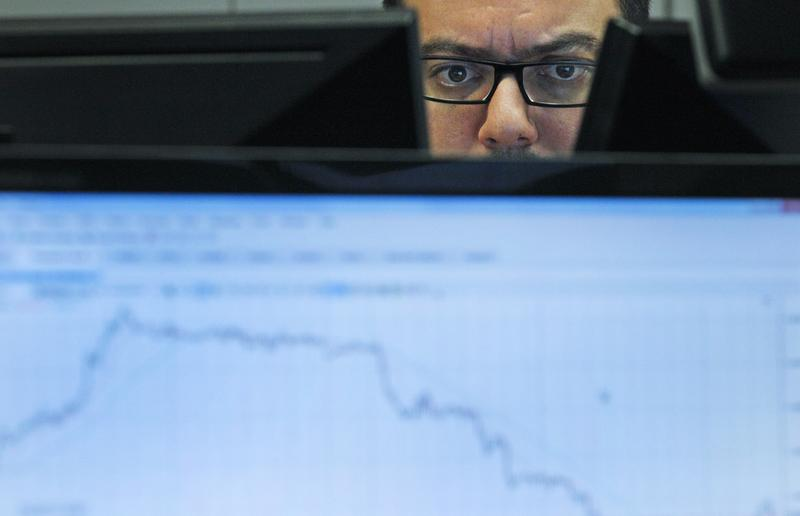 A Portuguese broker looks at computer screens in the trading room of a Portuguese bank Wednesday, Nov. 2, 2011 in Lisbon.