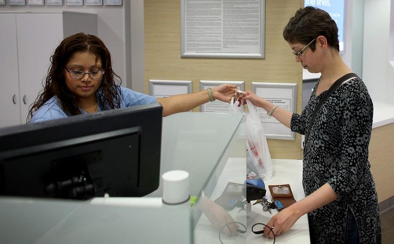 Mercedes Betaneo (L), a pharmacy technician for Walgreens, sells medicine at the Walgreens pharmacy to Christine Matthews who was using the insurance she purchased under the Affordable Care Act.