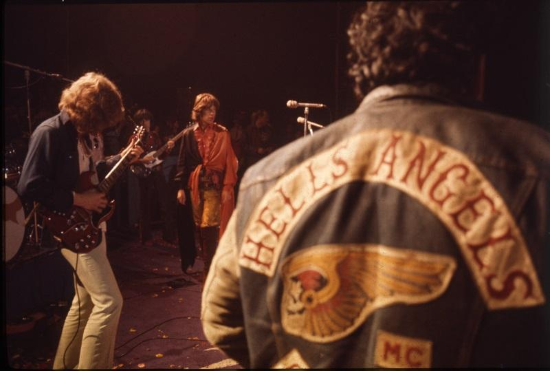 Left to Right: Mick Taylor, Mick Jagger, a Hells Angel at Altamont, 1969.