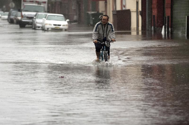 Beichen Li rides his bike down a flooded street after Hurricane Sandy, Oct. 30, 2012 in Hoboken, New Jersey.