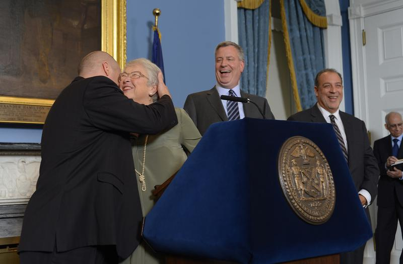 Schools Chancellor Carmen Farina hugging UFT President Michael Mulgrew as Mayor Bill de Blasio announced the teachers contract that included buy-outs for employees without permanent positions