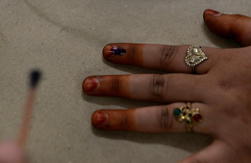 An Indian election officer marks the finger of a voter with ink at a polling station in New Delhi.