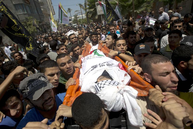 Palestinian mourners carry the body of Marwan Salem, a Palestinian militant who was killed during an Israeli air strike the night before, during his funeral procession on July 7, 2014 in al-Bureij ref