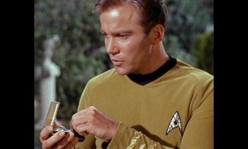 Captain Kirk using a communicator in <em>Star Trek</em>