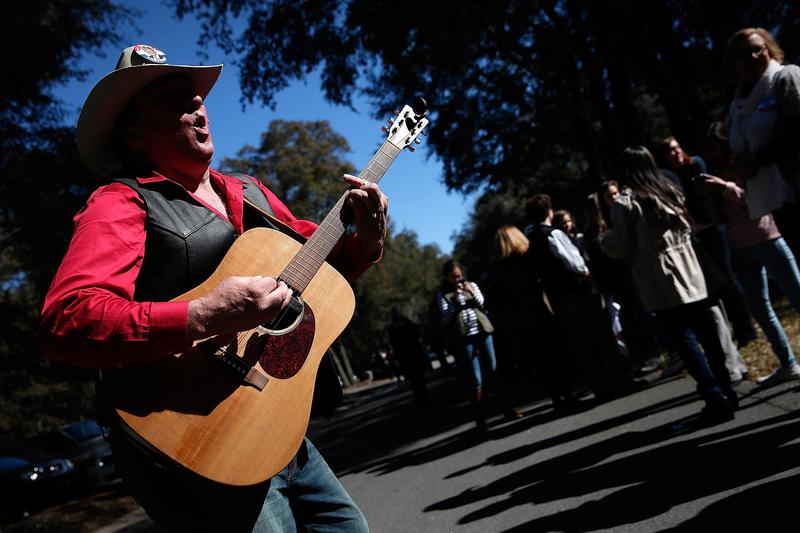 Musician and Trump supporter Kraig Moss sings and plays his guitar as South Carolina voters line up to hear Republican presidential candidate Donald Trump speak on February 19, 2016 in Pawleys Island