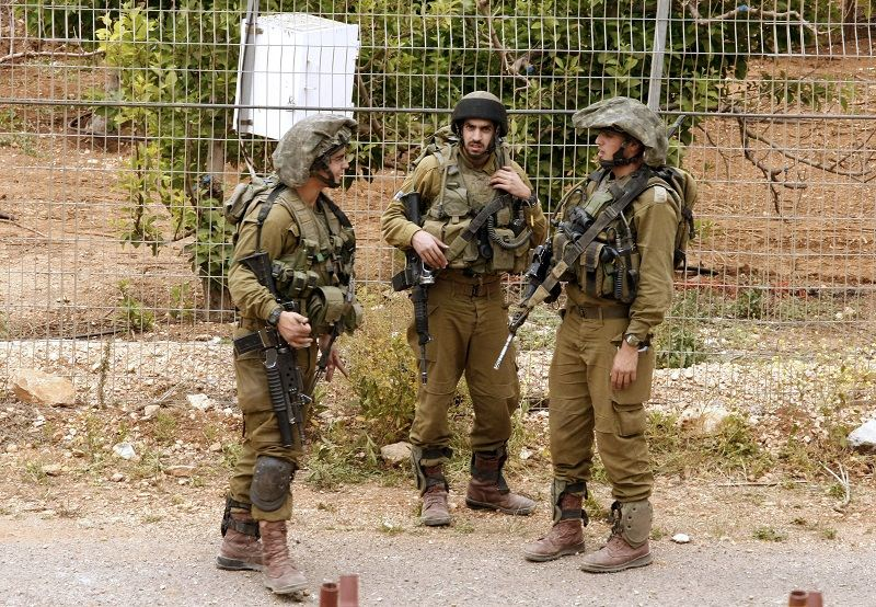 A picture taken from the Lebanese southern village of Kfar Kila shows Israeli soldiers standing on their side of the border on May 1, 2012.