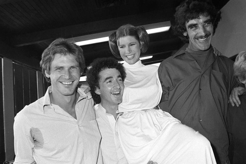 In this Oct. 5, 1978 photo, from left, actors Harrison Ford, Anthony Daniels, Carrie Fisher and Peter Mayhew take a break from filming the Star Wars television special