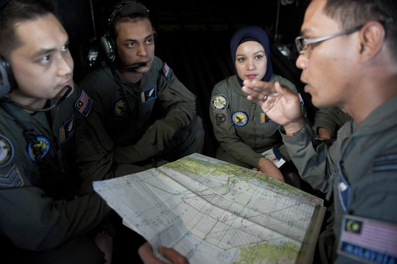 A Royal Malaysian Air Force Navigator captain Izam Fareq Hassan (R) talks with his team members onboard a Malaysian Air Force CN235 aircraft during a search and rescue operation.