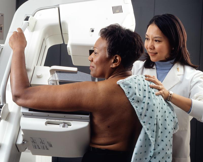 A woman receives a mammogram