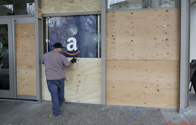 A man puts a wooden board over a window of the Student Union on the University of California, Berkeley campus in Berkeley, Calif.