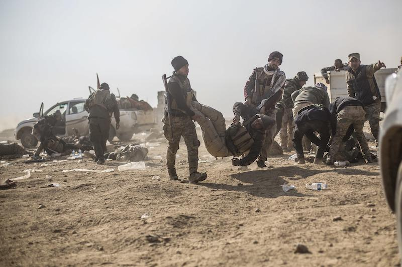 Iraqi soldiers of the 17th Division carry a wounded comrade after a mortar fell in an area where the troops where gathering to advance towards the Islamic State group held village of Ganus.