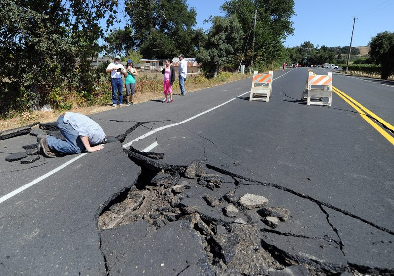 Nicholas George looks under a buckled highway just outside of Napa, California after earthquake struck the area in the early hours of August 24, 2014.