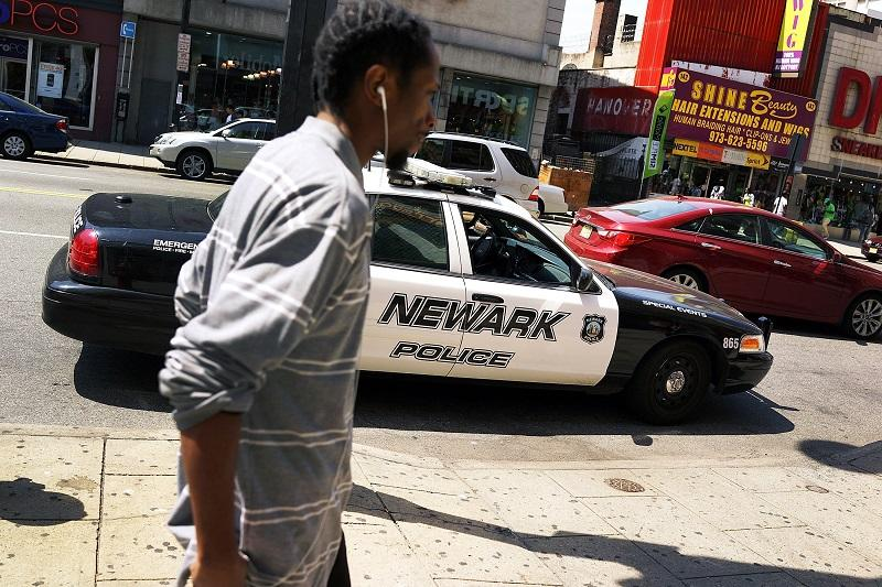 A man walks by a police car in downtown on May 13, 2014 in Newark, New Jersey.