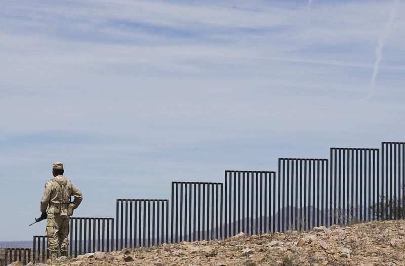 A Mexican soldier patrols along the U.S.-Mexico border wall on the outskirts of Nogales, Mexico, Tuesday, April 1, 2008. U.S.