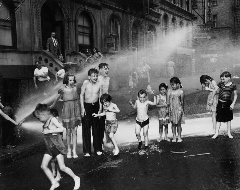Children cool down in the spray from a fire hydrant during a hot summer on New York's Lower East Side