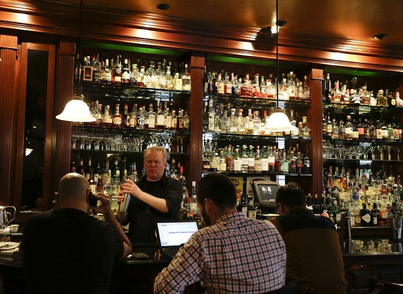 This Oct. 23, 2014 photo shows Mike Burrell works the bar at Daddy-O in New York. Daddy-O has been slinging whiskey since 1999 and offers over 200 bourbons.