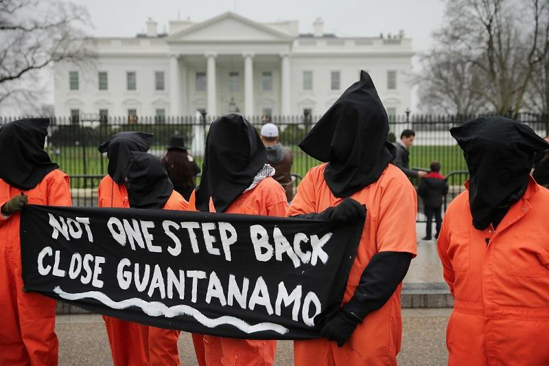 Demonstrators with the group Witness Against Torture dress in orange jumpsuits and wear black hoods while demanding that U.S. President Barack Obama close the military prison in Guantanamo, Cuba.
