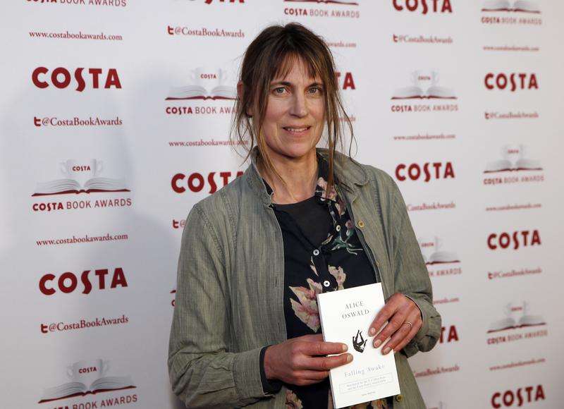 "Author Alice Oswald holds up her book ""Falling Awake"" as she poses for the media at the Costa Book Awards 2016 in London, Tuesday, Jan. 31, 2017."