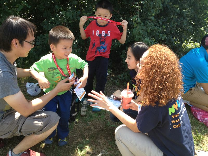 At the Hong Kong Dragon Boat Festival, outreach worker Jasmine Fernandez talks with Riy Xian about enrolling his son in pre-k.