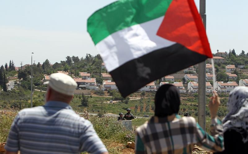 Palestinian protesters wave the national flag as they face-off with Israeli soldiers following a weekly demonstration against the expansion of settlements in the West Bank, on April 25, 2014.