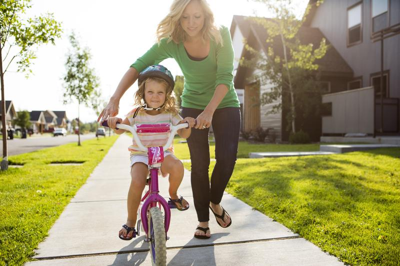 Mother teaching her daughter how to ride a bicycle.