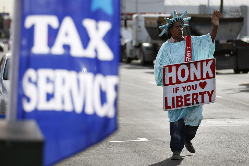A man dressed as the Statue of Liberty advertises a tax service.