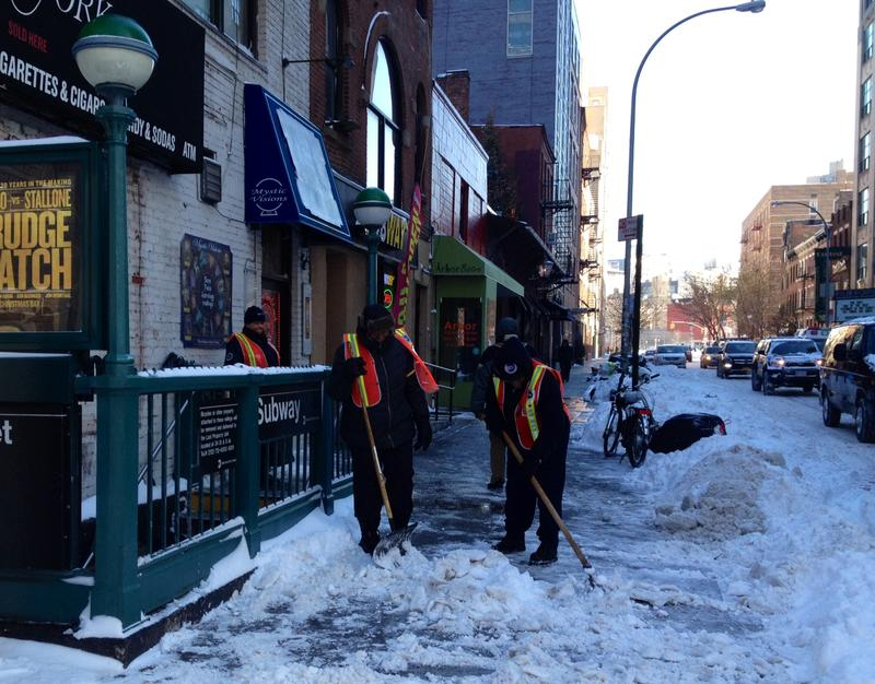 MTA workers clearing snow from a sidewalk outside the Houston Street subway station
