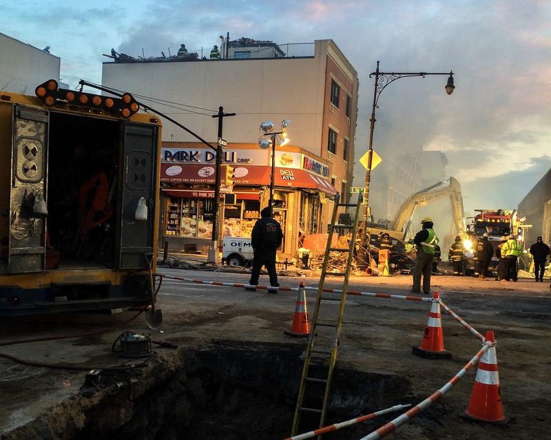 Fire continues to smolder one day after an explosion took down two buildings in East Harlem. Firefighters douse the blaze, while crews remove debris and officials search for a gas leak.