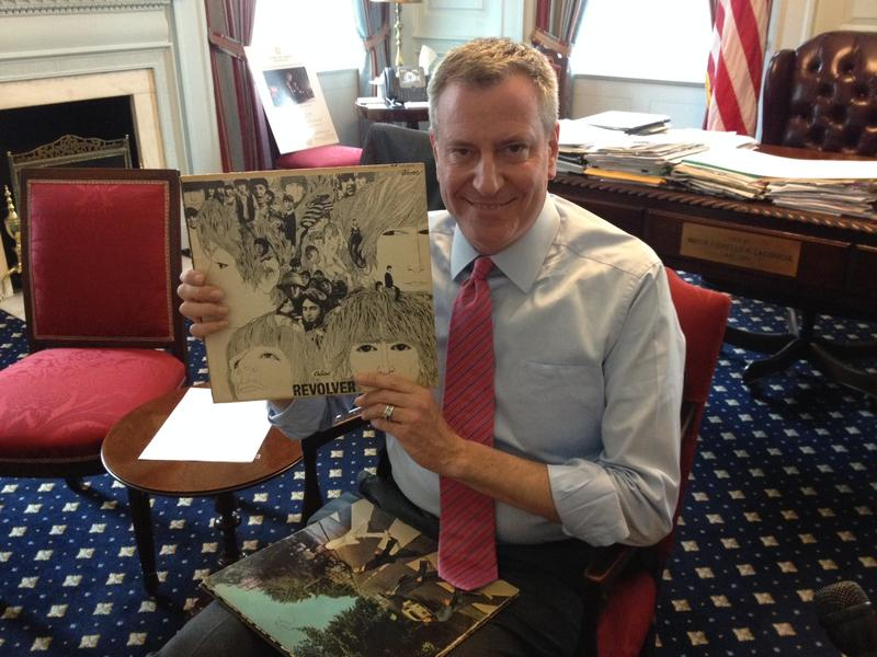 Mayor de Blasio in his office holding The Beatles album Revolver which is part of his collection currently in boxes at City Hall