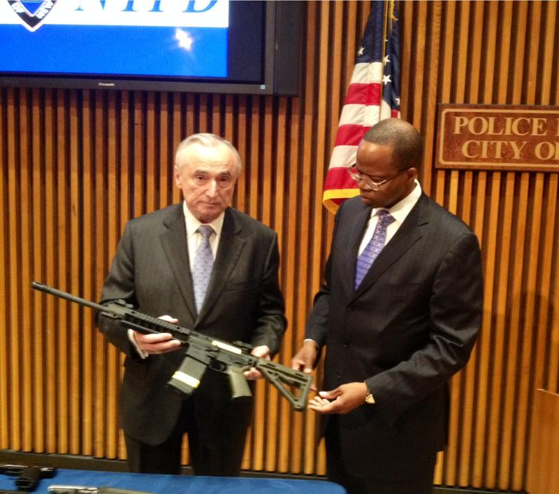 Police Commissioner Bill Bratton and Brooklyn D.A. Ken Thompson inspect one of the automatic weapons seized in the bust.