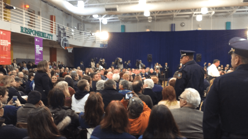 Police move to escort hecklers out of Gov. Chris Christie's town hall meeting in Mount Laurel, NJ. The governor is at right, in white, ignoring the hecklers.