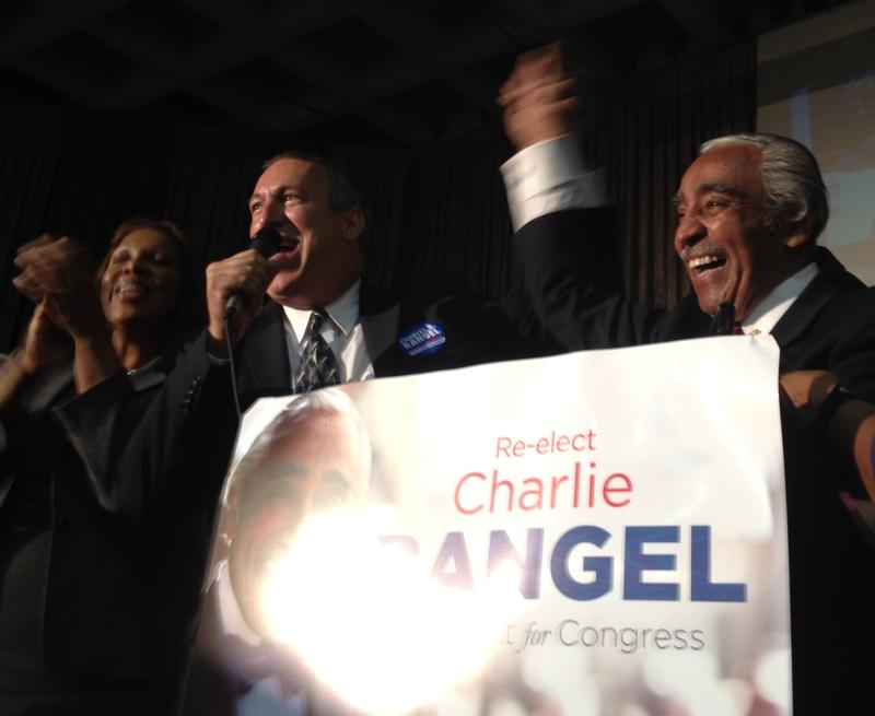 Public Advocate Tish James stands left of Adam Clayton Powell IV who raise Congressman Charlie Rangel's hand in the air