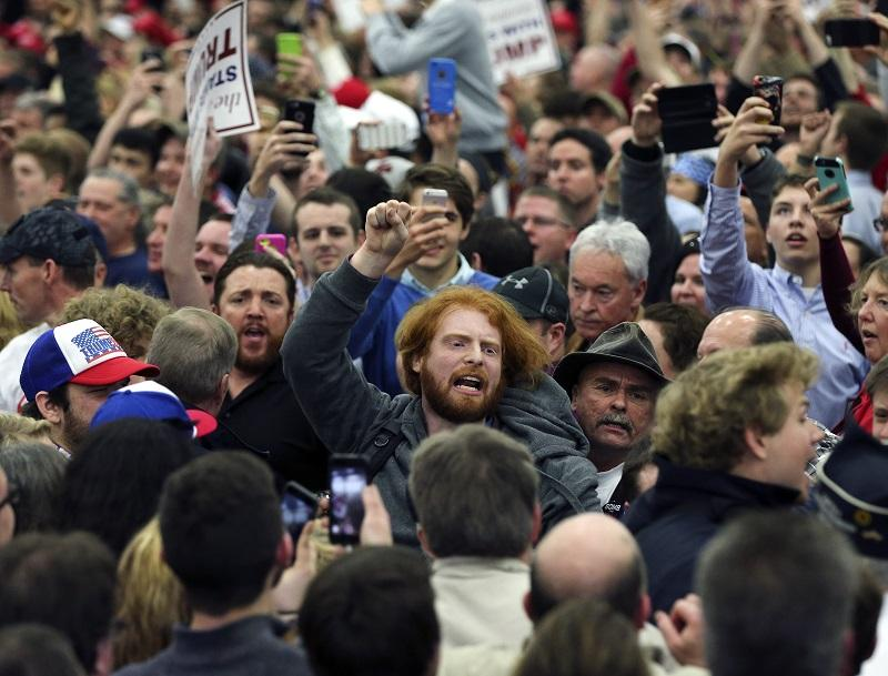 In this Tuesday, March 1, 2016 file photo, a protester is escorted out of a rally for Republican presidential candidate Donald Trump in Louisville, Ky.
