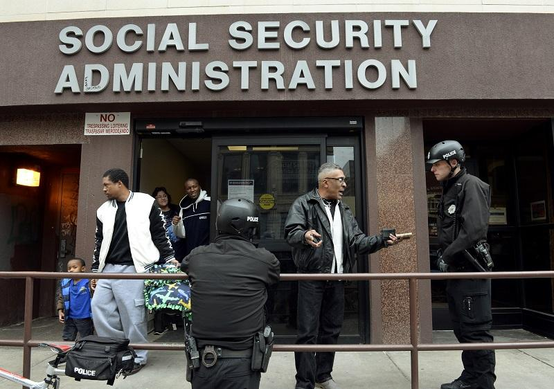 Denver Police Officer Robert Southern, right, and his partner Officer Darren Ulrich talk with Virgil McFarland outside the Social Security Administration offices in Denver, CO, 1/2015.