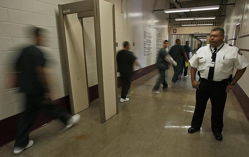 Inmates from California pass through a metal detector under the watchful eye of a guard at the Florence Correctional Center, a prison operated by Corrections Corporation of America in Florence, Ariz.